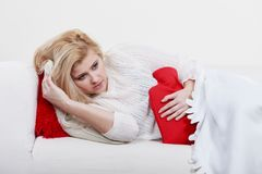 Woman feeling stomach cramps lying on cofa. Painful periods and menstrual cramp problems concept. Woman having stomach cramps lying on cofa feeling very unwell Royalty Free Stock Photos