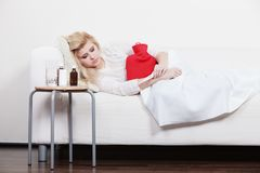 Woman feeling stomach cramps lying on cofa. Painful periods and menstrual cramp problems concept. Woman having stomach cramps lying on cofa feeling very unwell Stock Images