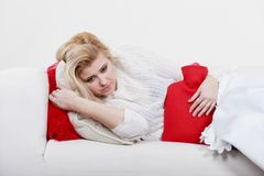 Woman feeling stomach cramps lying on cofa. Painful periods and menstrual cramp problems concept. Woman having stomach cramps lying on cofa feeling very unwell Royalty Free Stock Image