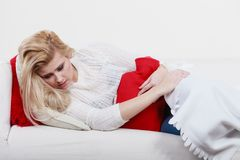 Woman feeling stomach cramps lying on cofa. Painful periods and menstrual cramp problems concept. Woman having stomach cramps lying on cofa feeling very unwell Royalty Free Stock Photo