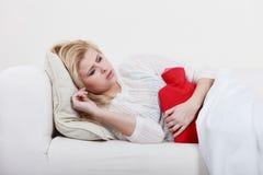 Woman feeling stomach cramps lying on cofa Royalty Free Stock Photos