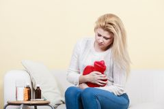 Woman feeling stomach cramps sitting on cofa Stock Photo