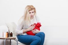 Woman feeling stomach cramps sitting on cofa Royalty Free Stock Image