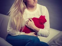 Woman feeling stomach cramps sitting on cofa Stock Photos
