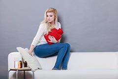 Woman feeling stomach cramps sitting on cofa Royalty Free Stock Image