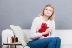 Woman feeling stomach cramps sitting on cofa Stock Images