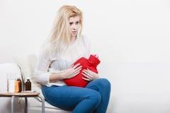 Woman feeling stomach cramps sitting on cofa Stock Image