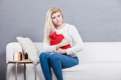 Woman feeling stomach cramps sitting on cofa Royalty Free Stock Photo