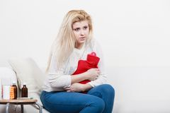 Woman feeling stomach cramps sitting on cofa. Painful periods and menstrual cramp problems concept. Woman having stomach cramps sitting on cofa feeling very Royalty Free Stock Photo