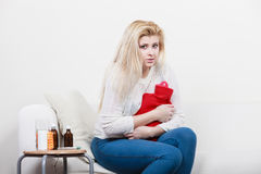 Woman feeling stomach cramps sitting on cofa Royalty Free Stock Photos