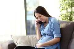 Painful pregnant woman calling doctor at home. Painful pregnant woman calling doctor sitting on a couch at home royalty free stock photos