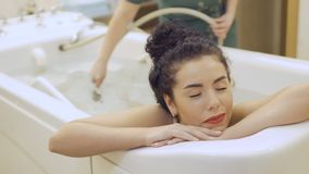 Painful procedure of hydromassage. Beautiful brunette in bikini lays in the bath in the spa. The doctor makes a hydromassage of body under water with shower stock video