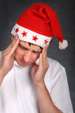Painful Teenager in Santas Hat Royalty Free Stock Photography