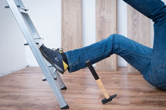 Painful worker after on the job injury. On the job injury of one worker fallen from a ladder Royalty Free Stock Image