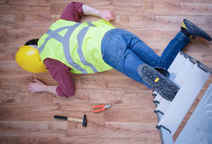 Painful worker after on the job injury. On the job injury of one worker fallen from a ladder royalty free stock images
