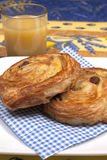 Pains aux raisins. And a glass of juice Royalty Free Stock Photos