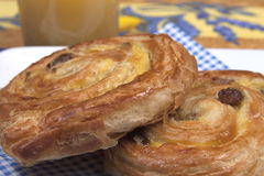 Pains aux raisins. And a glass of juice Royalty Free Stock Images