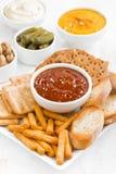 Pains, biscuits et sauces d'assortiment sur la table blanche Photographie stock libre de droits