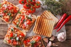 Pains grillés avec des haricots à une sauce tomate, à un fromage et à un plan rapproché d'herbes H Images libres de droits