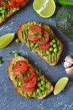Pains grillés avec l'avocat, les pois et les tomates photographie stock libre de droits