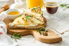 Pains grillés avec la poire, le fromage de chèvre et les noix, miel, romarin Images stock