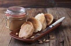 Pains grillés avec le beurre d'arachide d'un plat d'argile photographie stock