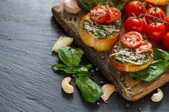 Pains grillés avec le sause et les tomates de pesto Photographie stock libre de droits