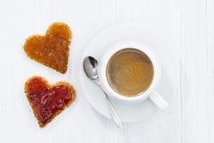 Pains grillés dans la forme de coeur avec de la confiture de fruit et la tasse de café Photo libre de droits