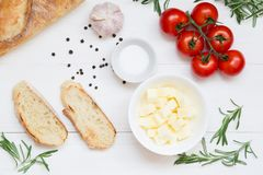 Pains grillés italiens de bruschette avec les tomates et le fromage sur le fond en bois blanc, vue supérieure photo libre de droits