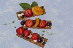 Pains grillés sains et savoureux avec le formage caillé, les fruits et les baies sur un fond bleu image libre de droits