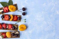 Pains grillés sains et savoureux avec le formage caillé, les fruits et les baies sur un fond bleu photo stock