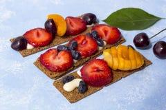 Pains grillés sains et savoureux avec le formage caillé, les fruits et les baies sur un fond bleu images stock