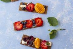 Pains grillés sains et savoureux avec le formage caillé, les fruits et les baies sur un fond bleu photos libres de droits