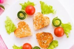 Pains grillés sous forme de coeur, de cerise et de concombre d'un plat Image stock