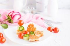 Pains grillés sous forme de coeur, de cerise et de concombre d'un plat Photographie stock libre de droits