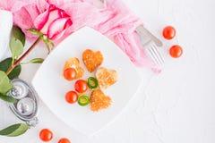 Pains grillés sous forme de coeur, de cerise et de concombre d'un plat Photographie stock