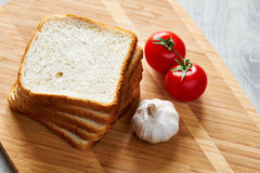 Pains grillés sur le conseil et les légumes images stock