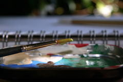 Paint. Art brush rested on a paint palette by a watercolor book Royalty Free Stock Photos