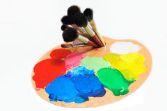 Paint. Artist palette  and paintbrushes on the white background Royalty Free Stock Photography