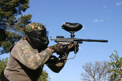 Paint ball  fun. Man shooting a paint ball gun with helmet and face shield on Royalty Free Stock Photos