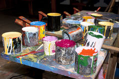 Paint bottles, brushes and paint cans. In an art studio royalty free stock photos