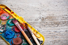 Paint box and paint brush. Messy, used watercolor paint box and paint brush Royalty Free Stock Photos