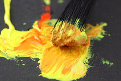 Paint and brush. Paint being mixed with paint brush on black paper Stock Photography