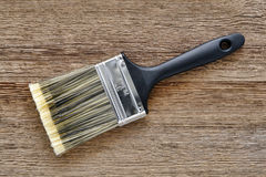 Paint Brush on Aged Wood Boards Painter Workbench. New nylon paint brush with black plastic handle and fine natural bristles on aged textured weathered wood Stock Images