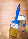 Paint brush with blue handle standing near can on Stock Photography