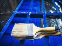 Paint brush on blue metal wall background Stock Photography