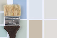 Paint Brush Brown Handle on Color Chips. Overhead shot of  a paint brush with a brown handle laying on a sheet of color samples. Horizontal format with copy Royalty Free Stock Image