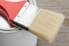 Paint brush and can. Red paint brush on paint can on wooden plank - home renovation or diy concept Royalty Free Stock Photography