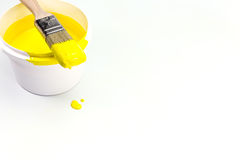 Paint brush on a can with yellow paint Stock Photo