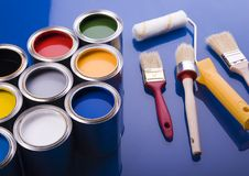 Paint brush and cans. Cans with paint and brushes on the blue background royalty free stock images